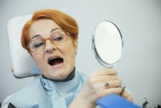 woman looks at her teeth in mirror