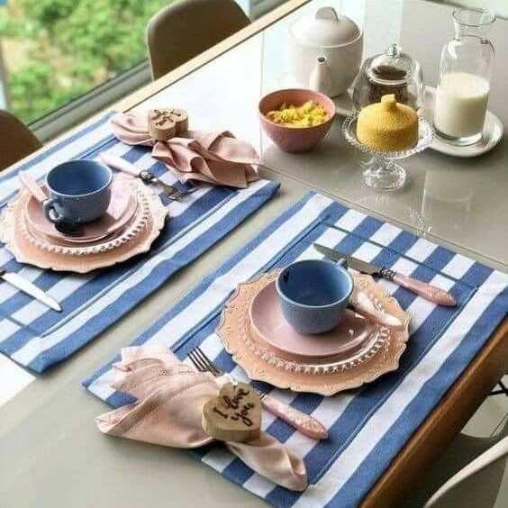 Mesa posta de café da manhã, com pratos rosas e xícaras azuis.