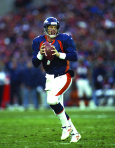 John Elway drops back to pass against the Seattle Seahawks at Mile High Stadium in Denver, CO on December 27, 1998.