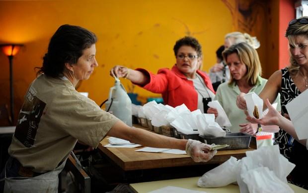 (CM) FEXXCOOKIELADY_CM7 Debbie Kuehn (left) hands ...