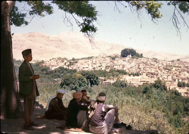 """A group of Afghan men look out over Istalif, about 18 miles northwest of Kabul, which was a centuries-old center of pottery making as well as other tourist attractions. The village was nearly destroyed by major fighting between """"Northern Alliance"""" forces and the Taliban in the late 1990s."""