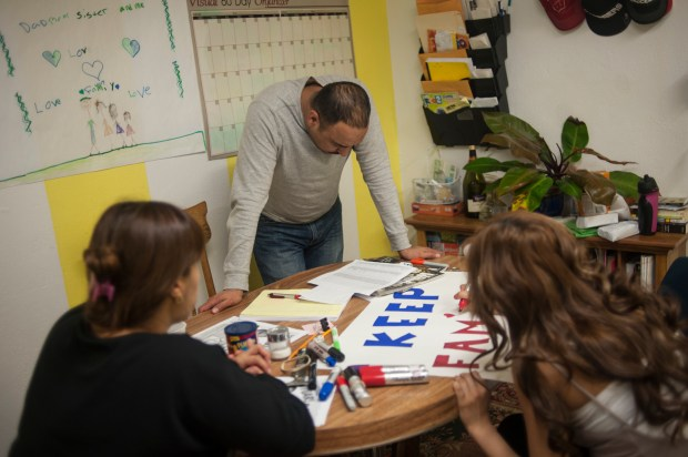 Arturo Hernandez Garcia takes a moment while making calls to supporters, inviting them to participate in an upcoming rally. In the foreground are his wife Ana Sauzameda (Left) and daughter Mariana, 15.