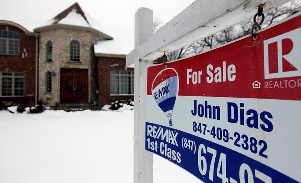 """A """"for sale"""" sign is seen outside a home in Glenview, Ill."""