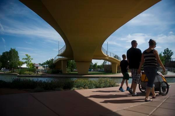 A family walks under Veterans' Bridge, located at the Historic Arkansas Riverwalk of Pueblo. The city has plans to expand the area.