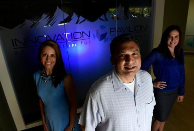 Vic Ahmed, chairman of Innovation Pavilion, middle, is pictured with Suzy Gutierrez, left, and Kerrianne Leffew, at the company's Centennial headquarters on June 4, 2015.