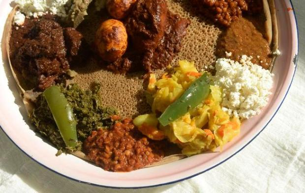 The injera, an Ethiopian flat bread, is set underneath a variety of traditional Ethiopian foods as Ethiopian families gather at a home in Aurora for a meal on Tuesday July 28, 2015.
