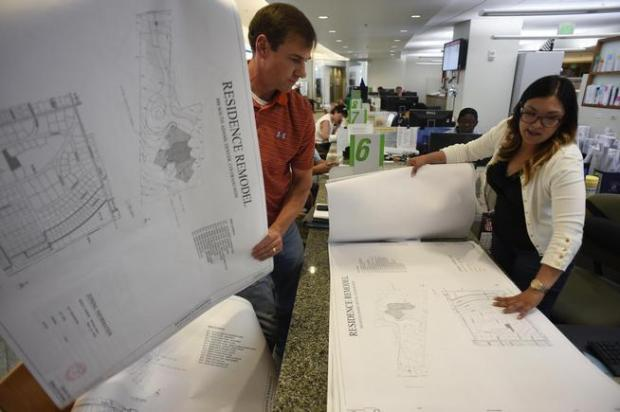 Contractor Randy Henckel, left, works with plan review technician Nadine Garcia to get building permits for a demolition and remodel for a new home at the Development Services building permit office in Denver's Webb municipal building in August 2015. (Denver Post file)