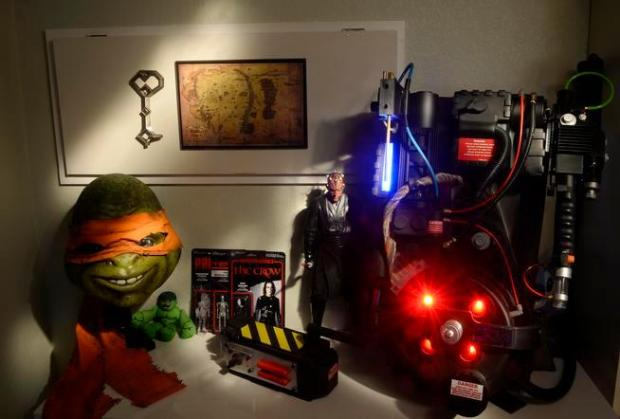 "Joshua Viola's Broomfield home, with many of his '80s and '90s genre movie memorabilia. The Teenage Mutant Ninja Turtle ""Michelangelo"" is left with a proton pack, right, from ""Ghostbusters."""