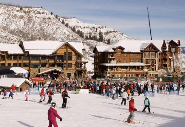 Skiers and snowboarders ride down the Village Express lift at Snowmass Ski Area's created base village area.