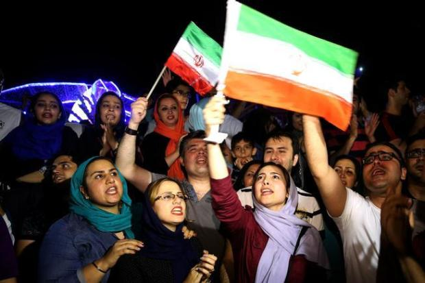 In this July 14, 2015 file photo, jubilant Iranians celebrate a landmark nuclear deal in Tehran, Iran. World powers and Iran struck a historic deal to curb Iran's nuclear program in exchange for billions of dollars in relief from international sanctions.