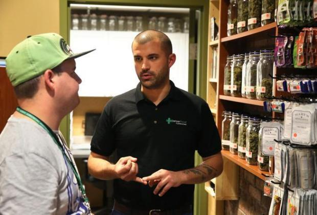 In this Aug. 25, 2014 photo, marijuana store Denver Relief co-owner Kayvan Khalatbari, right, talks with his employee Jeff Botkin his medical and recreational marijuana shop in Denver. Khalatbari also runs Denver Relief Consulting, which assists current and would-be marijuana-related businesses around the country, as well as owning a chain of pizza restaurants in Denver.
