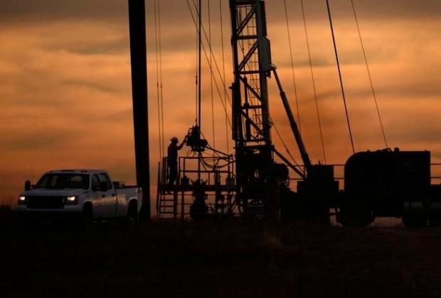 An oil-field worker starts his day's work before the sun rises over an oil rig near Kersey in 2014.