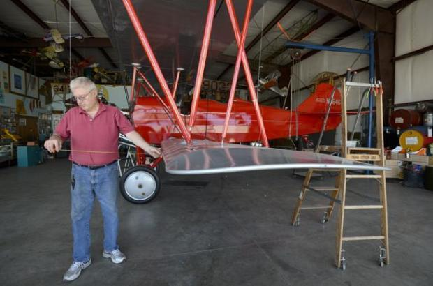 Daniel Murray checks the wing alignment of a 1928 Travel Air biplane at his hangar at the Vance Brand Municipal Airport in June 2012.