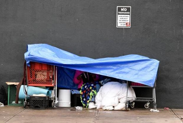 DENVER, CO - MARCH 7: A homeless person stays dry underneath a tarp with his belongings along Park Ave West in Denver, Colorado on March 7, 2016 in Denver, Colorado. The city of Denver plans to clear out homeless camps in the Ballpark neighborhood. Notices were put up to inform the homeless that they needed to move their belongings along city streets. Salvatore, who said he was a first responder at Ground Zero during 9/11 as a concrete excavator, says he suffers from COPD and fibrosis from being at Ground Zero for over 14 months. (Photo by Helen H. Richardson/The Denver Post)
