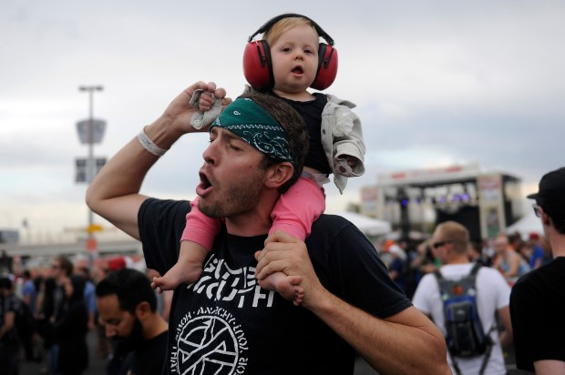 DENVER, CO - SEPTEMBER 21: Preston Purviance holds up his daughter, Arralyn Murray-Purviance's, 10 months, hand as they dance to the sounds of Me First and the Gimme Gimmes during the final day of Riot Fest at Sports Authority Field at Mile High on September 19, 2014 in Denver, Colorado. Riot Fest wrapped up its second year in Colorado on Sunday at Sports Authority Field. (Photo by Seth McConnell/The Denver Post)