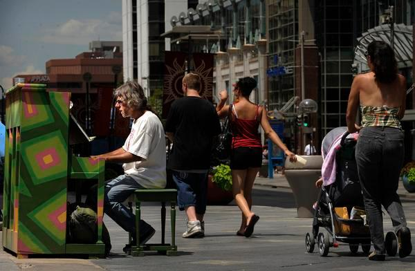 A man plays one of the public pianos on Denver's 16th Street Mall as visitors walk past.