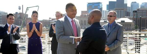 Paul Washington, left center, shakes hands with Denver Mayor Michael Hancock on the Millennium Bridge in 2011 after being named city economic development director.