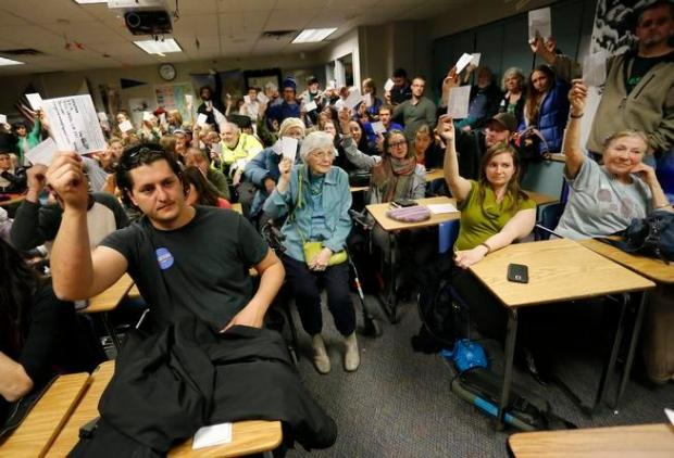Members of a precinct gathered in a crowded schoolroom raise their hands, signifying a vote, during the Democratic caucus, in Boulder on March 1.