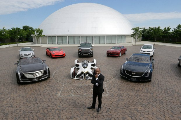 In this June 9, 2016, photo, Ed Welburn, head of global design for General Motors, stands next to company concepts and production vehicles on the grounds of the company's Technical Center in Warren, Mich. During a visit to the Philadelphia Auto Show, a then 9-year-old Welburn was spellbound by the 1959 Cadillac Cyclone, with its big fins and rocket-like front cones. Then and there, he vowed to become a designer for GM. Welburn said he's retiring on June 30. (AP Photo/Carlos Osorio)