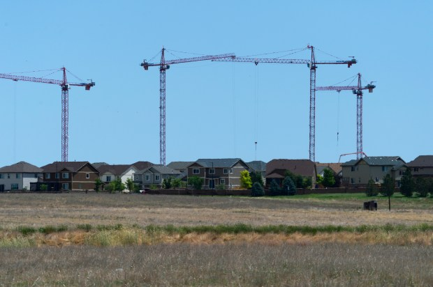 Gaylord Rockies Resort and Convention Center construction cranes behind a housing development.