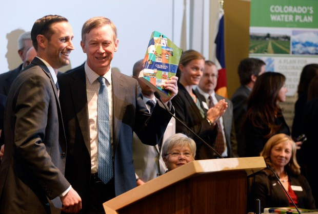 Gov. John Hickenlooper holds up a copy of Colorado's Water Plan during an announcement about the plan on Nov. 19, 2015.