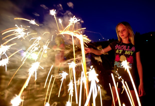 Sparklers1.jpg Audrey Hester, 12, watches her sparkler glow while waiting for the fireworks start at the Denver National Golf Club in Erie, Colorado July 3, 2011. Times-Call File /Mark Leffingwell
