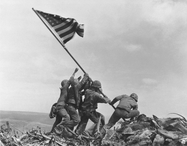 Marines of the 28th Regiment, 5th Division, on Feb. 23, 1945, raise the American flag atop Mount Suribachi in Iwo Jima, Japan.