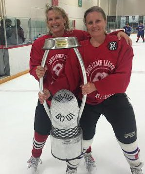 Heather Karas, widow of Jeff Karas, a former Littleton Hawks and Colorado Select hockey coach, hoists Dawg Nation's women's division championship trophy with Butch Mousseau's widow Macaire Mousseau. Jeff Karas died of leukemia in 2013 and Butch Mousseau of head trauma in March. Photo provided by Heather Karas
