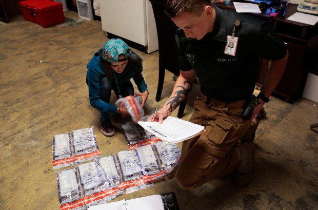 INEWS101-MarijuanaBanking11272014.jpg Dominic Powelson of Blue Line Protection Group, right, picks up cash from Brooke Dingess at a Strainwise marijuana store in Denver on Nov. 17, 2014. Legal marijuana businesses are a cash-heavy operation and many rely on armored car services like Blue Line for cash transportation and protection. (Joe Mahoney/Rocky Mountain PBS I-News)