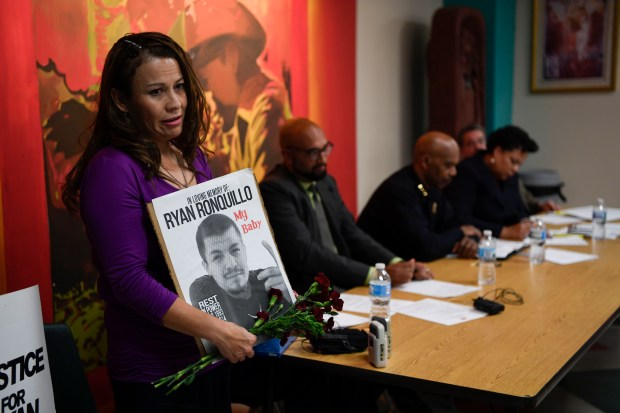 DENVER, CO - JUNE 08: April Sanchez addresses the community as she holds a sign in memory of her son Ryan Ronquillo, who was shot by DPD in 2014, during the Colorado Latino Forum discussion June 8, 2016 at Escuela Tlatelolco to discuss the impact of police shootings in the Latino community. The police chief and safety director will share the stage with two mothers who have lost their sons in police shootings. (Photo By John Leyba/The Denver Post)