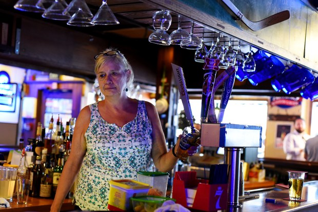 Owner Nanette Nelson pours a beer at Shelby's Bar and Grill on Friday. Nanette and her husband Howard have owned the local establishment for 25-years. (Photo by Kira Horvath/ The Denver Post)