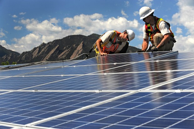 Workers install solar panels on a roof in Boulder.