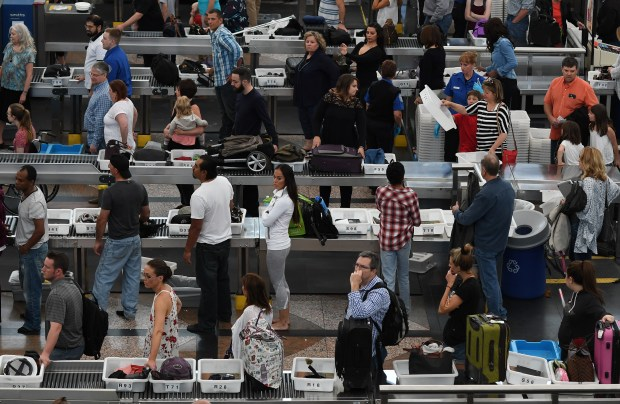 Travelers at Denver International Airport make their way through security lines