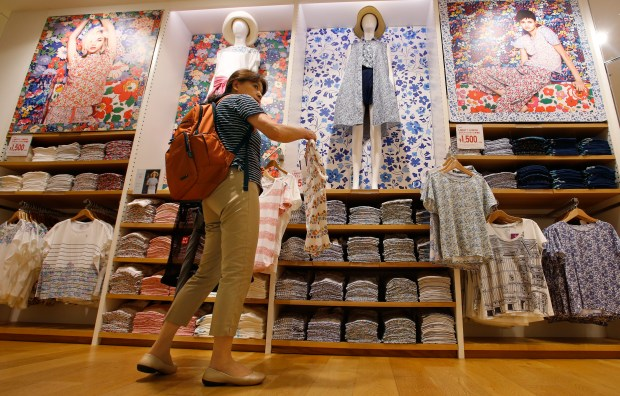 In this June 9, 2016 photo, a shopper looks at items at Uniqlo's flagship store in Tokyo's Ginza shopping district. Japanese clothing company Uniqlo, a 17-nation 1,734-store empire that has thrived on a formula of churning out variations of colors and sizes of simple items like fleece tops and polo shirts. But now, the company hopes to become the world's biggest apparel maker and is hiring foreign talent to add fashion flair and arty collaborations to its already established reputation for using technology in materials and fabrics. It also wants to grow globally. (AP Photo/Shizuo Kambayashi)