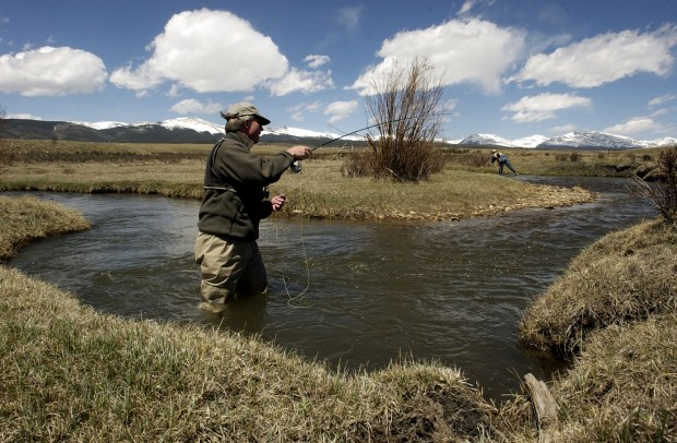 Park County,COLORADO-May 11, 2004-Gary Nichols , Tourism and Community Development Director, Park County, fly fishes on Fourmile Creek in South Park. This stream, on a private ranch, is one of several now being offerered for public fishing through the South Park Fly Fishers. The program, funded by a grant from Great Outdoors Colorado, allows a few people a day to fish private waters through a permitting process. The program helps the ranchers financially too. Upstream (to the right) of Gary is Dieter Erdmann , Conservation Real Estate Specialist for Colorado Open Lands. The snow covered mountains of the Mosquito Range are in the background. (DENVER POST PHOTO BY LYN ALWEIS) (Photo By Lyn Alweis/The Denver Post via Getty Images)