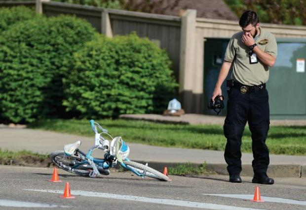 An investigator with the Boulder County Coroner's Office pauses for a moment while looking a Peyton Knowlton's bike after the 8-year-old was killed by a motorist at on Alpine Street on May 20. (Matthew Jonas / Staff Photographer)