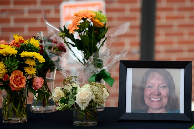 A photo of Cara Russell and flowers sit on a table during a vigil June 30. Russell was shot and killed by her estranged husband, Mickey Russell, at her office in Lower Downtown Denver.