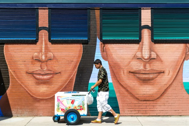 DENVER, CO - JULY 07: Lorenzo Chavez, 15, pushes his ice cream cart in front of a mural at Mestizo-Curtis Pool in Five Points on Monday, July 07, 2014 in Denver, CO. While partly cloudy, temperatures soared to 99F during the day driving many families to find ways to keep cool. (Photo by Kent Nishimura/The Denver Post)