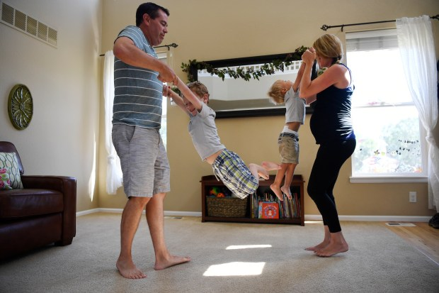 PARKER, CO - July 13: Andrew Willson, left, and his wife Lindsey, right, play with their kids, Breck, 4, second from left, and Bowan, 2, third from left, in their living room July 13, 2016. Bowan suffers from food allergies that potentially require the use of EpiPen auto-injectors in an emergency, the Willson's have several on hand to handle any potential problems, but find themselves scraping to pay for the very expensive pens. (Photo by Andy Cross/The Denver Post)