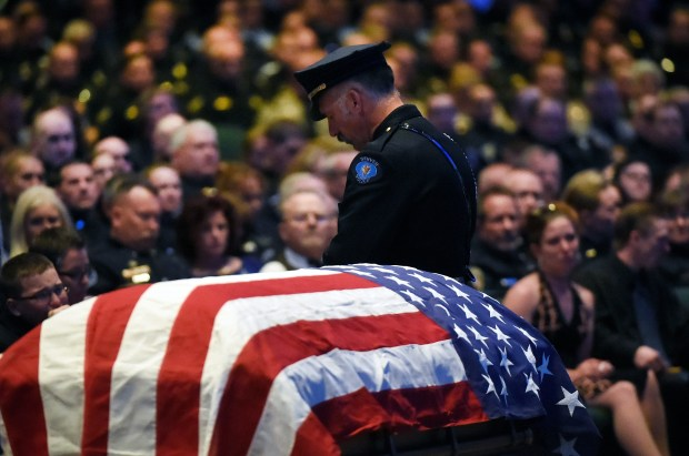 "A Denver police officer stands watch over the flag-draped casket at the memorial service for Park County Deputy Corporal Nathaniel ""Nate"" Carrigan at Faith Bible Chapel on March 14, 2016 in Arvada, Colorado."