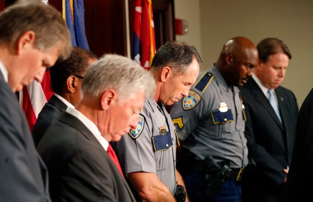 Baton Rouge police chief Carl Dabadie, Jr. center, bows his head in prayer with other officials at the start of a news conference at police headquarters in Baton Rouge, La., Wednesday, July 6, 2016.