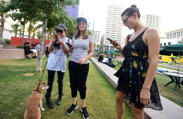 Three friends look at their cellphones while playing Pokemon Go on July 13 at Pershing Square in Los Angeles, one of a number of landmark locations across communities in southern California serving as gathering point for people playing the game.