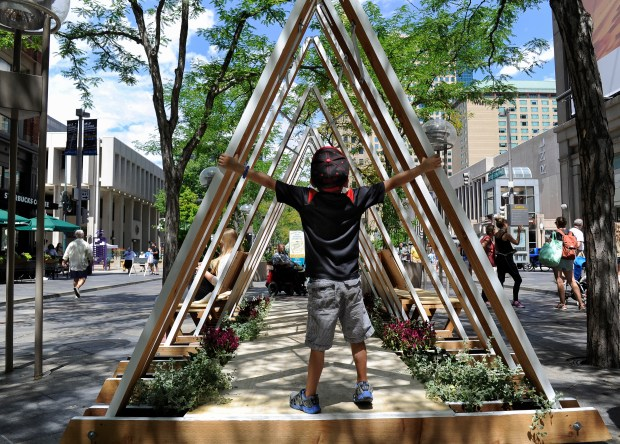 Colton Kostalnick, 6, from Golden grabs hold of the Peak1Six prototype by Shears Adkins Rockmore Architects. The Prototyping Festival takes place in downtown Denver along the 16th Street Mall on Saturday, July 23, 2016.