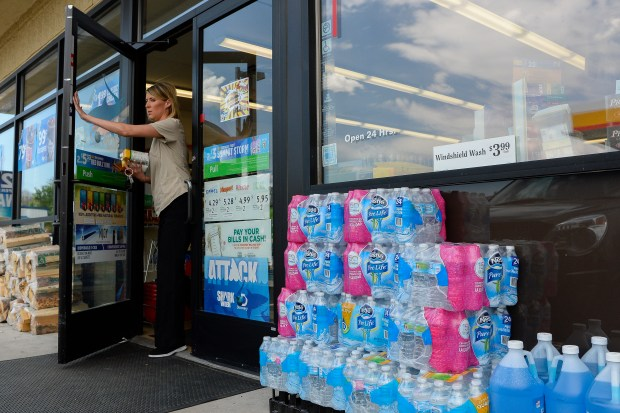 COLORADO SPRINGS, CO - JUNE 8: Packages of water bottles sit outside a local 7-Eleven Gas Station as a customer leaves the building on June 8, 2016. A invisible toxic chemical has been discovered in the drinking water that affects 70,000 people in the communities south of Colorado Springs. (Photo by Michael Reaves/The Denver Post)