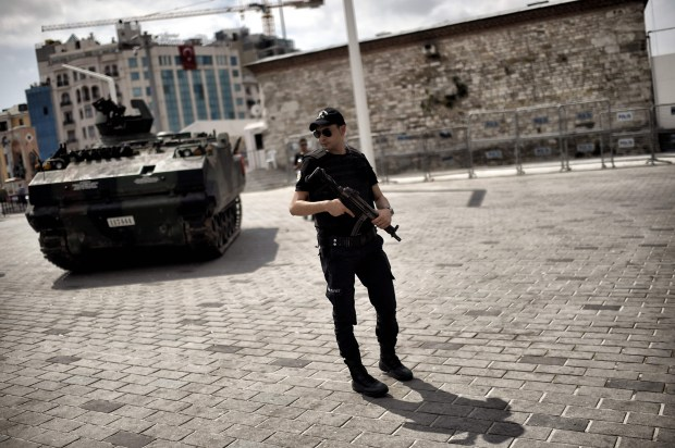 A police officer stands next to an armored vehicle that was used by soldiers during last week's coup attempt at Taksim square in Istanbul on Sunday.