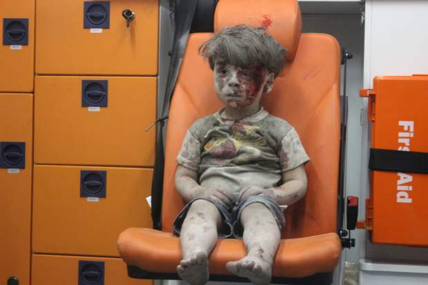 A 5-year-old Syrian boy covered in dust and blood sits in an ambulance after being rescued from the rubble of a building hit by an airstrike in Aleppo on Aug. 17.