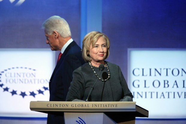 Former Secretary of State Hillary Clinton stands at the podium as former President Bill Clinton leaves the stage during a session of the Clinton Global Initiative, part of the Clinton Foundation, on September 22, 2014, in New York City.