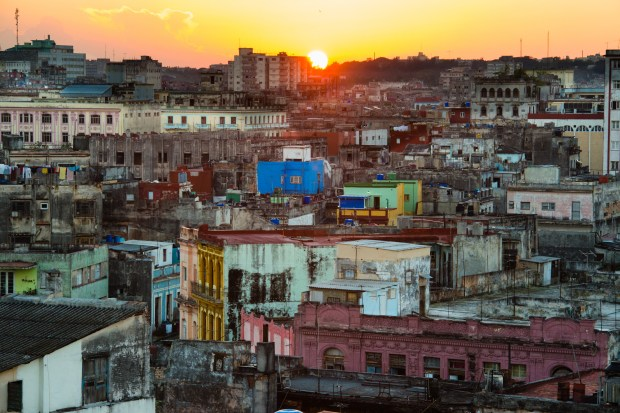 The skyline of Central Havana is seen from a rooftop in Old Havana. High above the tourists and old cars, laundry flies in the wind and people live in makeshift shacks.