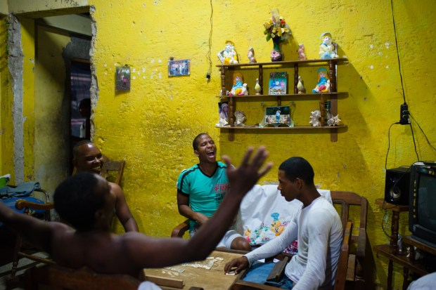 Friends play dominoes in the home of Yasmany Garcia, 26, center, in Camagüey, Cuba.