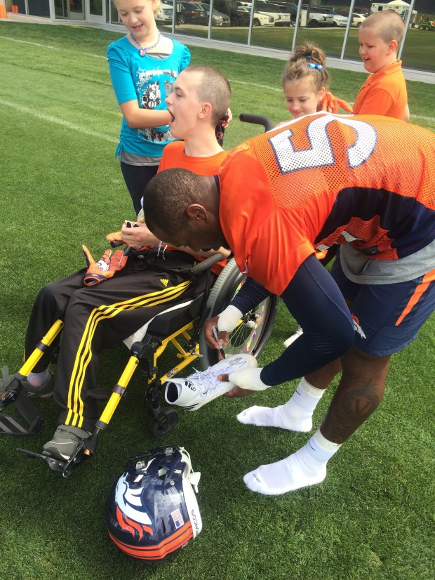 Von Miller takes off his shoes and gloves to sign and give to 14-year-old guest, Mathew Standwood Monday, August 8, 2016.
